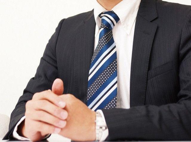両手を机の上で組むビジネスマン