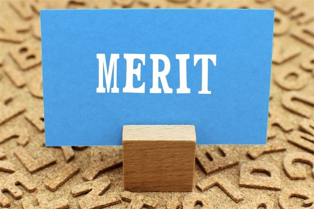 メリットと印字された青い紙を挟む積み木