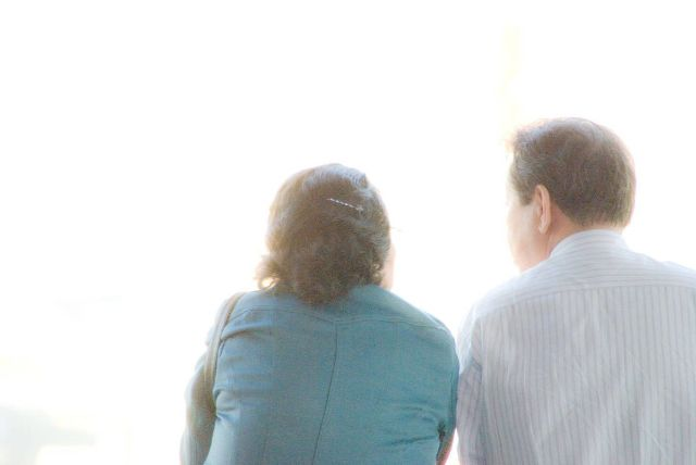 肩を並べて座る老夫婦の後ろ姿
