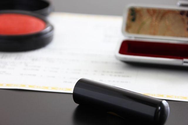 テーブルに置かれた紙の上にある朱肉と印鑑