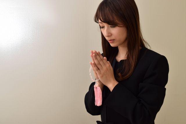 黙祷をする喪服姿の女性